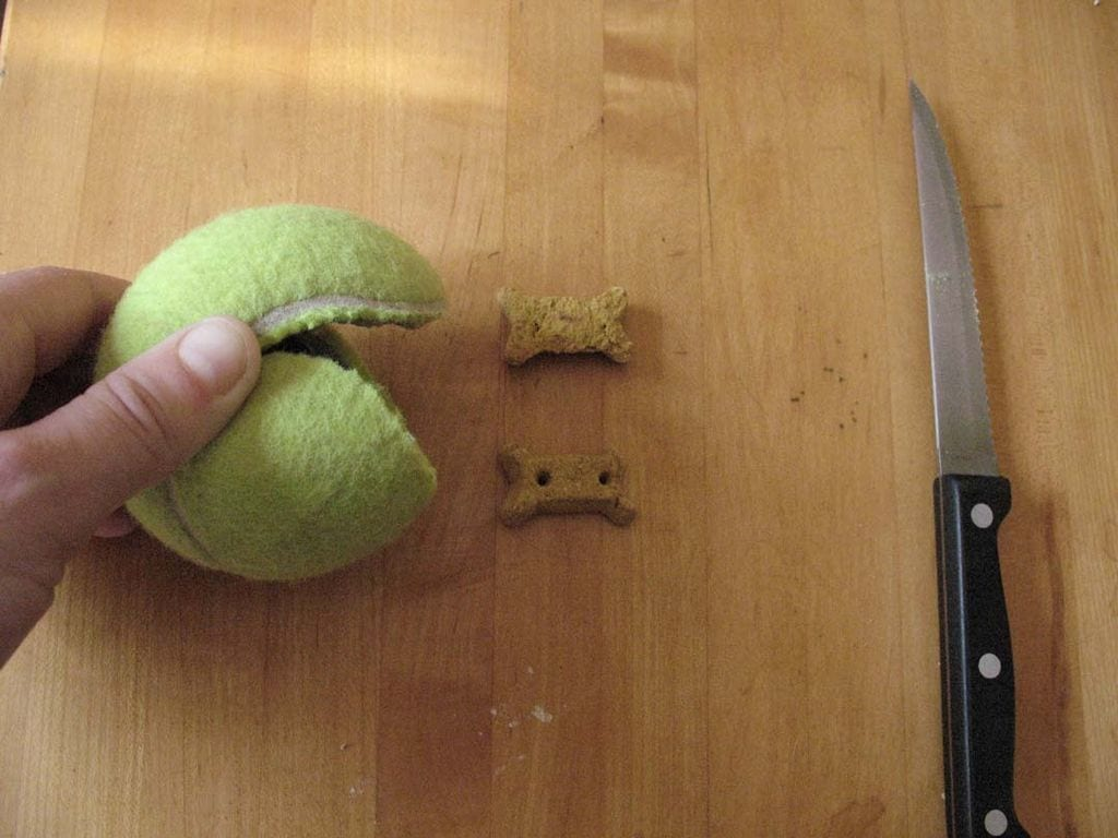 tennis ball cut open laying next to 2 dog treats and a knife