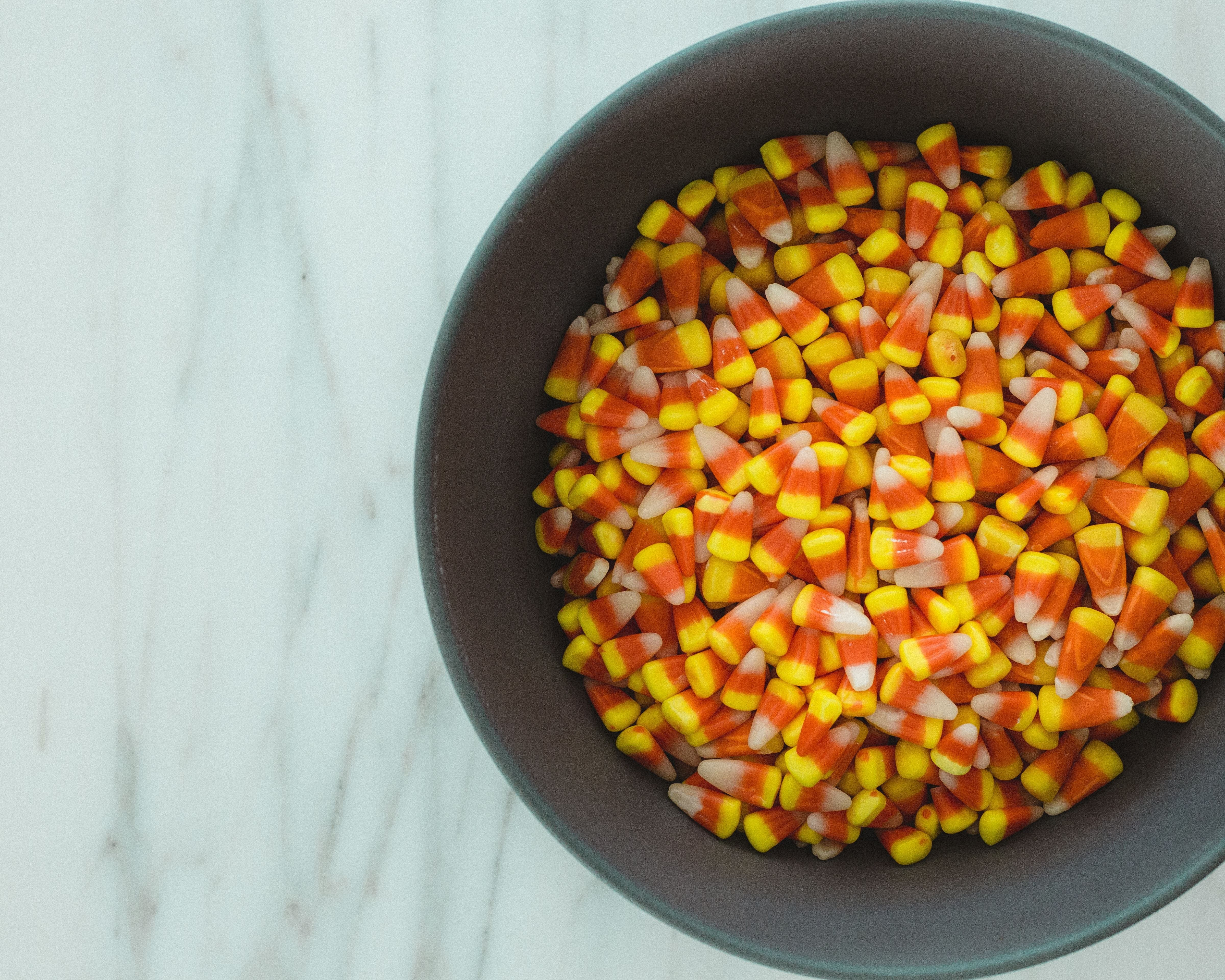 candy corn in a dark grey bowl on a marble counter top