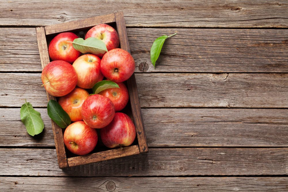 Apples in wooden crate on wood table top