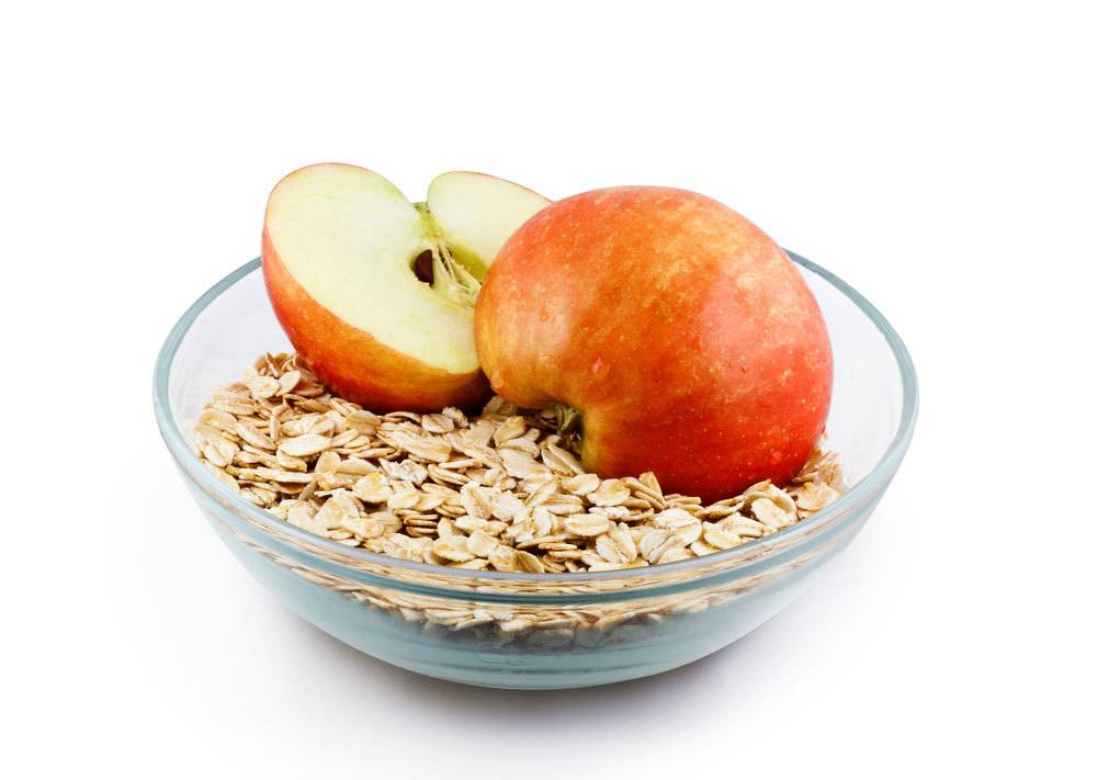 Bowl of oats with an apple on top cut in half