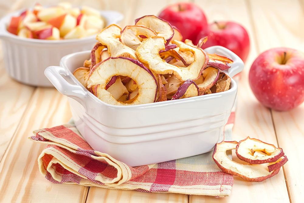 Apple chips in a casserole dish on wood table with scattered appleas and a red and white tea cloth