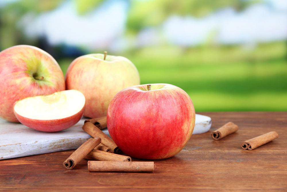 Apples and cinnamon sticks on a wooden table top with nature background