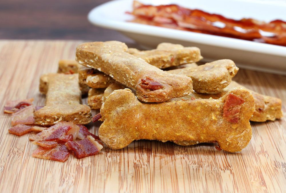 dog bone shaped dog treats with crumbled bacon and a plate of bacon in the background