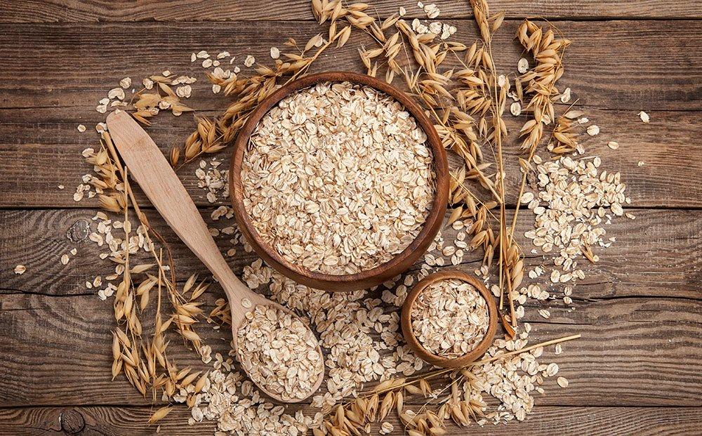 Oats spread on a wood surface  with a wooden spoon and bowl full of oats