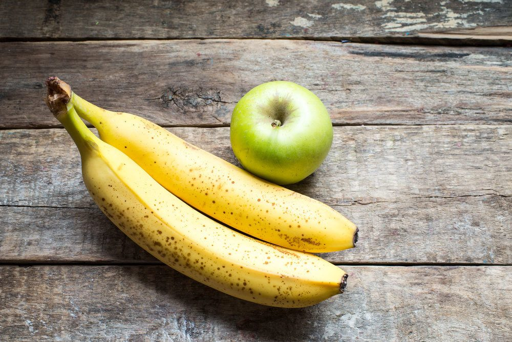 single green Apple and 2 bananas on wooden table