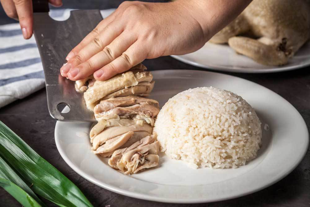 Person sliding chopped chicken onto plate of rice using a butcher knife