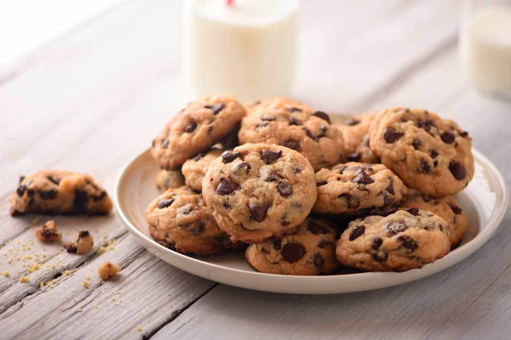 Plate of chocolate chip cookies with a glass of milk on a wooden table top