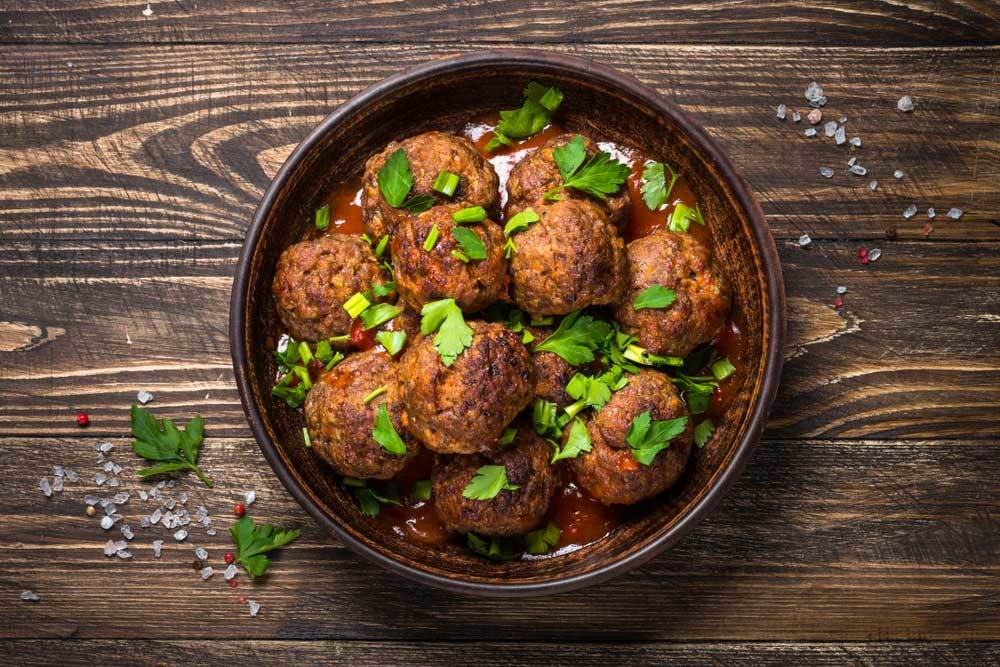Bowl of meatballs topped with parsley on wooden table top