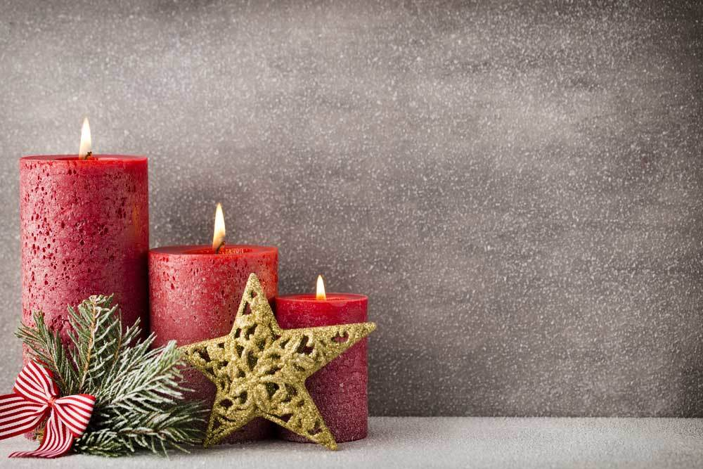 3 red pillar candles with a gold star ornament and pine branch bundle
