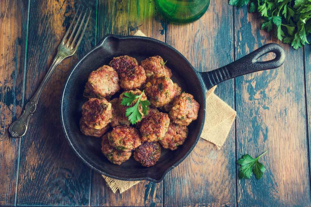 Meatballs in a cast iron skillet on a wooden table top with a tarnished fork