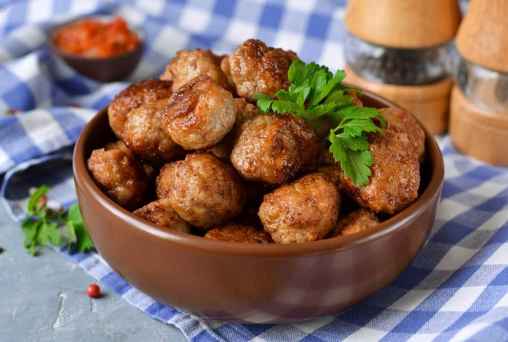 Bowl of meatballs on blue check tablecloth