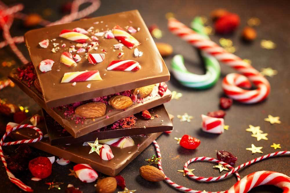 stack of peppermint bark chocolate  on table surrounded by candy canes and variety of decorations