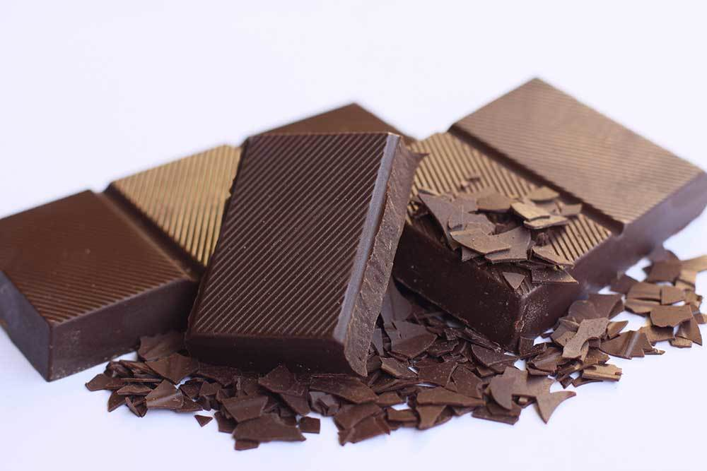 squares of chocolate with chocolate shavings on white background