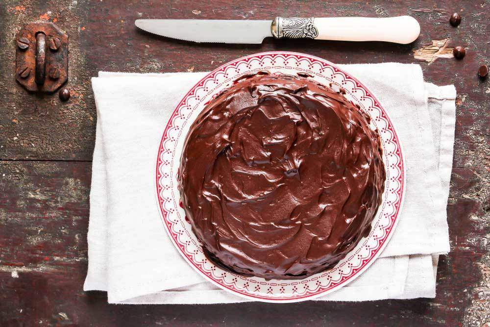 top view of a circular cake with dark rich icing on a decorative red and white plate resting on a tea towel on a wooden surface