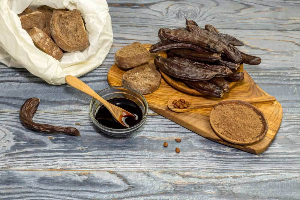 Variety of Carob products arranged on a wooded table top