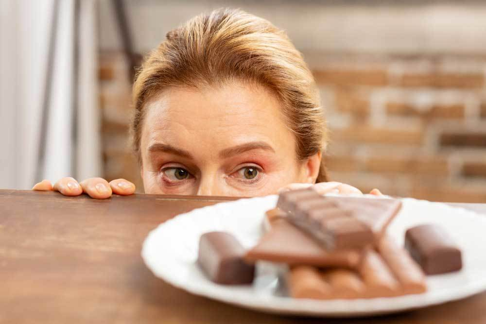 Woman peeking over edge of table at a plate of chocolate