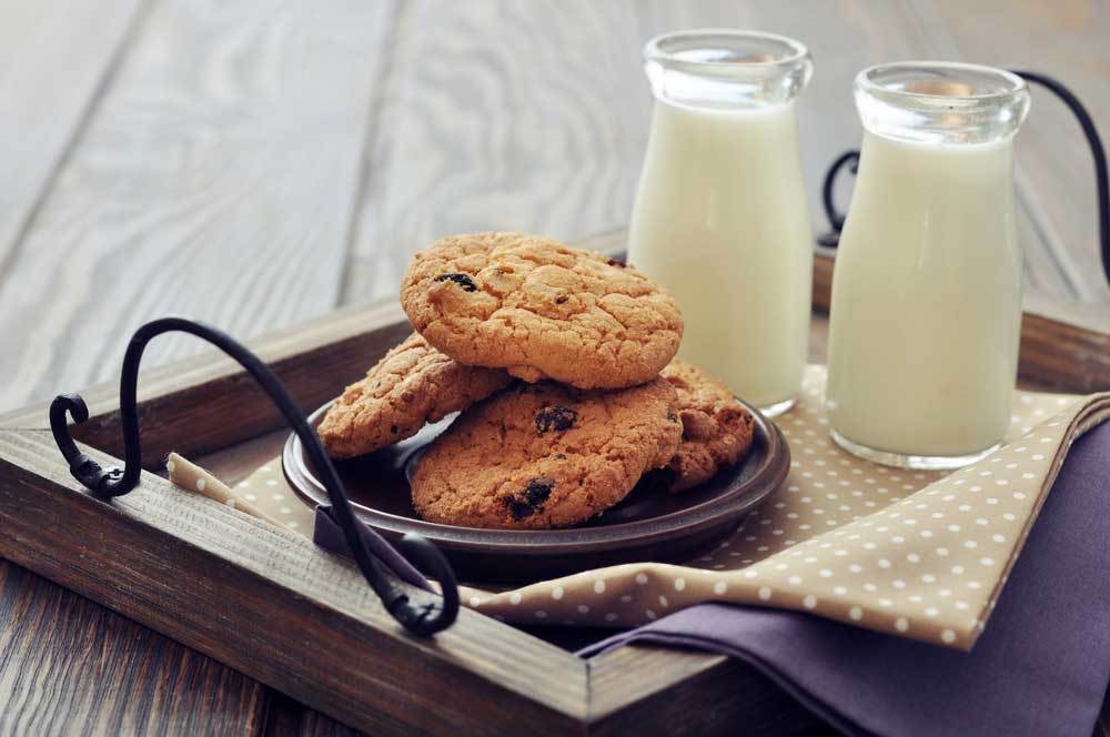 Cookies and milk on a wooden tray with 2 cloth napkins