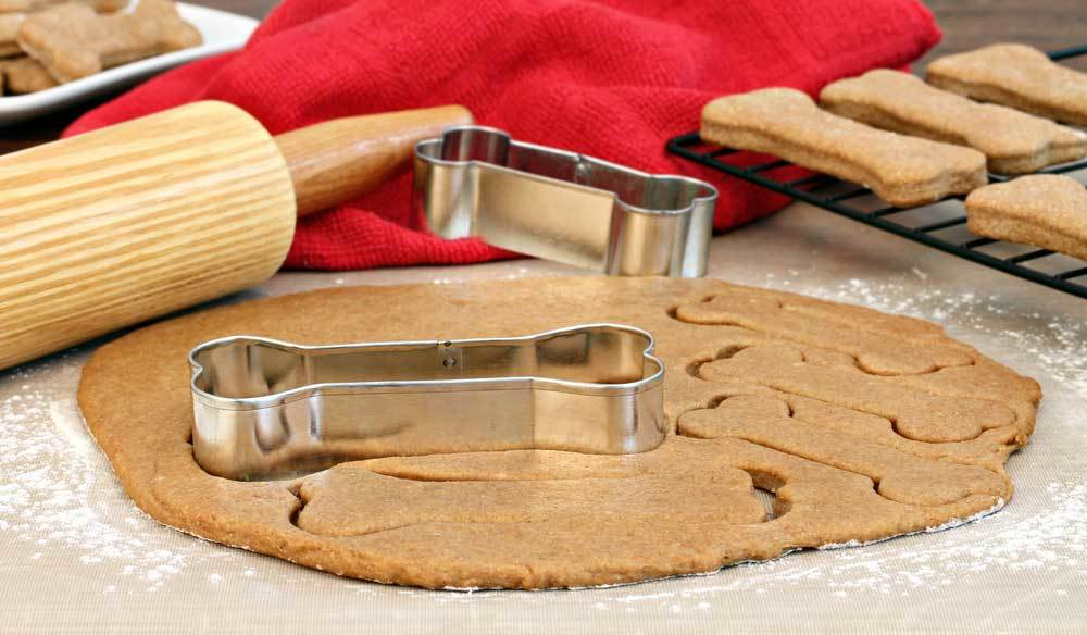 dough rolled on floured surface with dog bone cookie cutter, rolling pin, red towel, and rack of dog biscuits cooling.