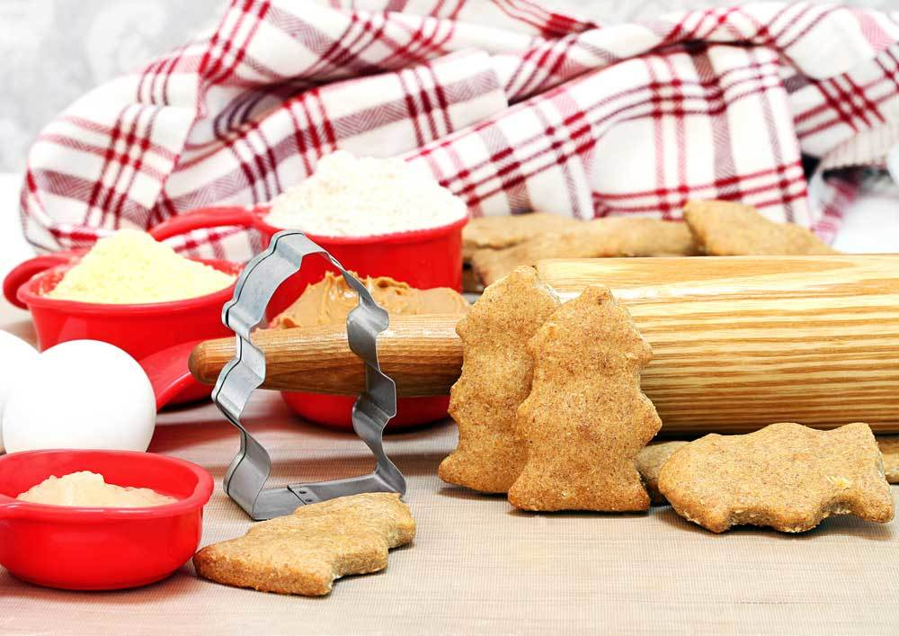 Fire Hydrant shaped cookies and cookie cutter with red plaid towel in background and red bowls of ingredients