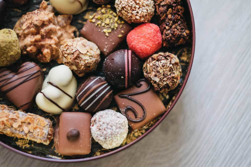 Variety of chocolate candies arranged on a plate on a wooden surface