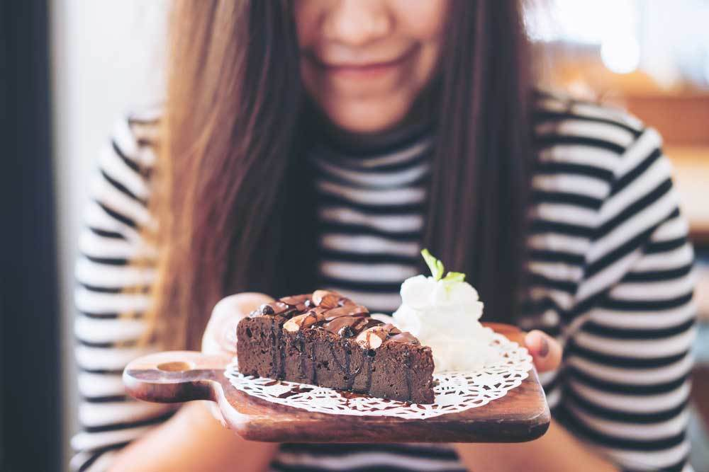 woman holding a plate containing chocolate cake and smiling
