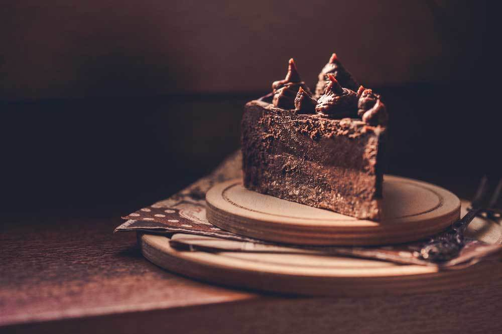 slice of carob cake with carob icing on wooden plate with a dark background