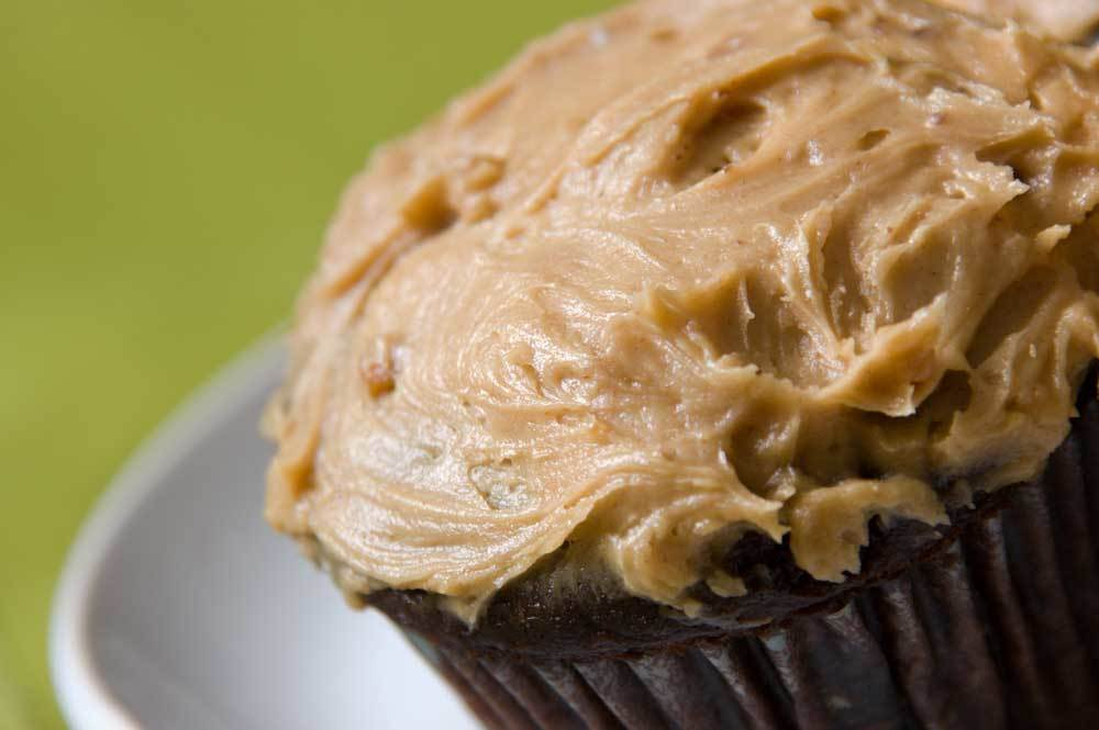 carob cupcake with peanut butter frosting on white plate on green background