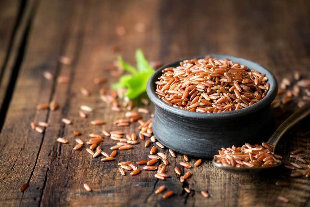 Red Rice  in a small black bowl on a wooden table