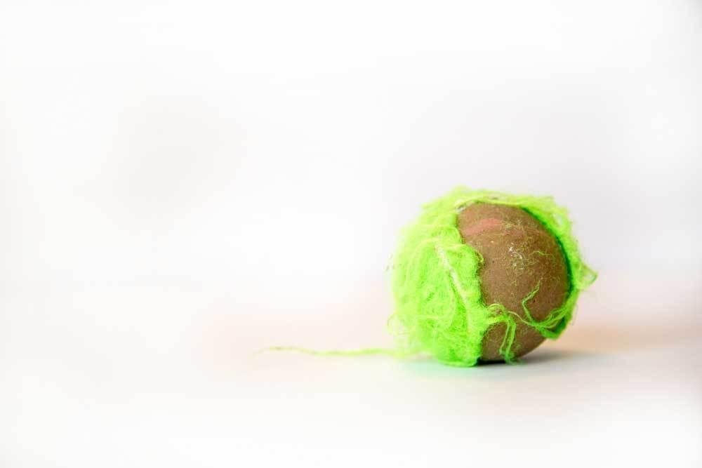 A chewed tennis ball missing half of its felt on a white background