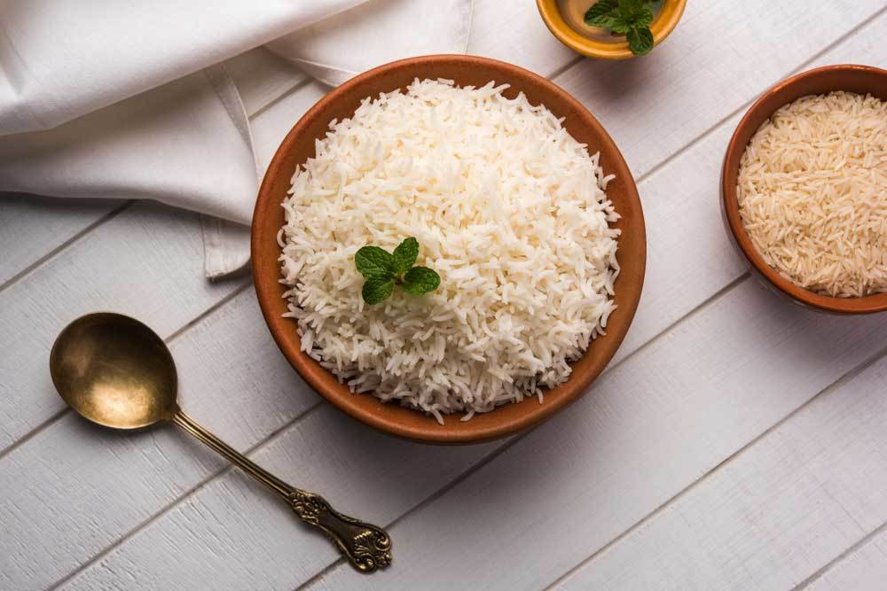 Wooden bowl of cooked rice with mint garnish and tarnished silver spoon