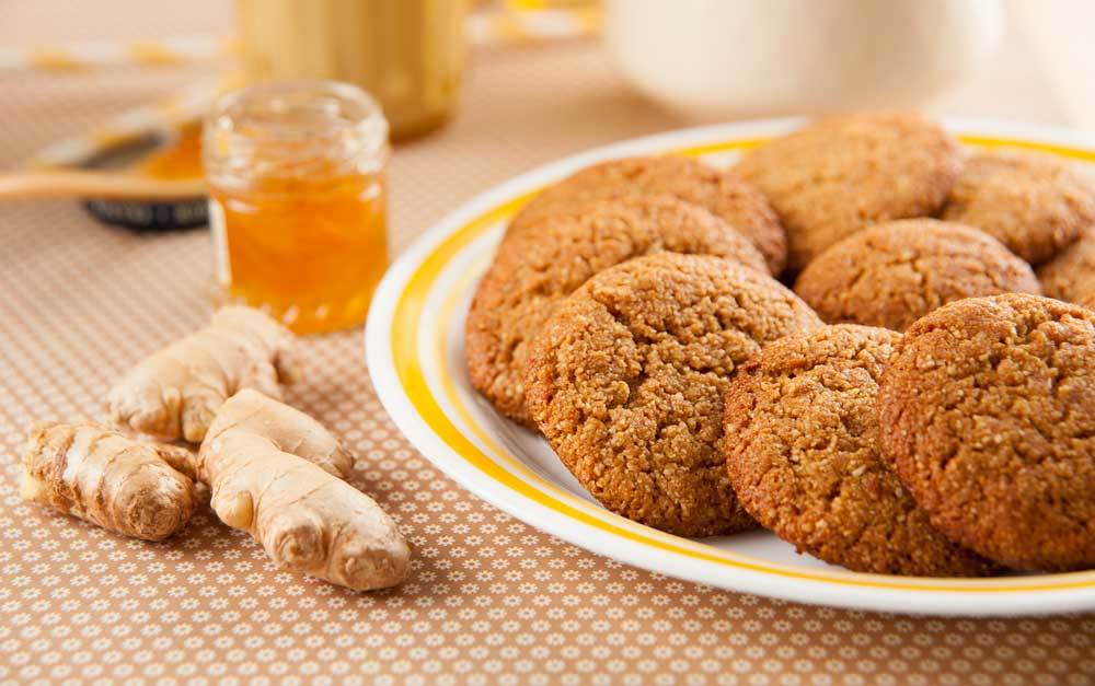 Plate of Ginger Cookies on a cloth covered table with a jar of honey and piece of ginger root
