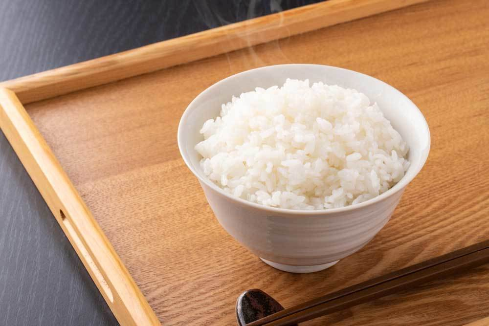 Bowl of cooked white rice resting on wooden serving tray