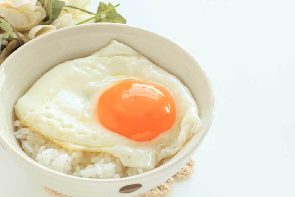 White bowl full of white rice with sunny side egg on top