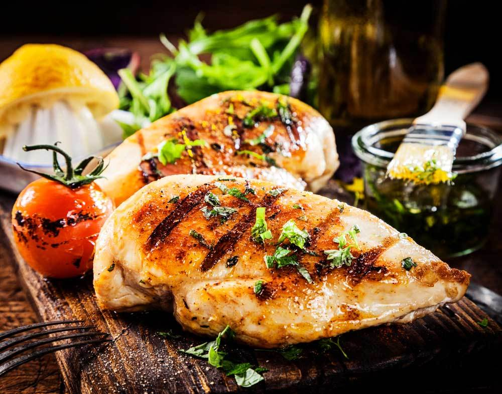 grilled chicken breast on a cutting board with vegetables