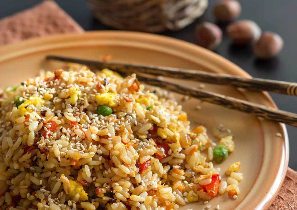 brown rice and vegetable mix on brown plate with chopsticks