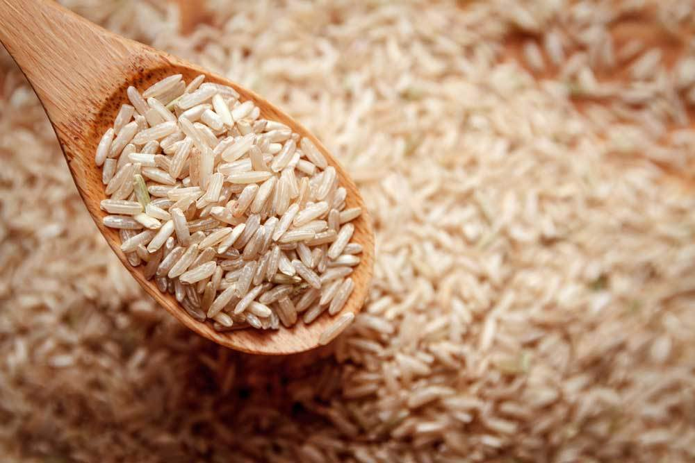 a wooden spoon full of dried brown rice over a pile of dried rice