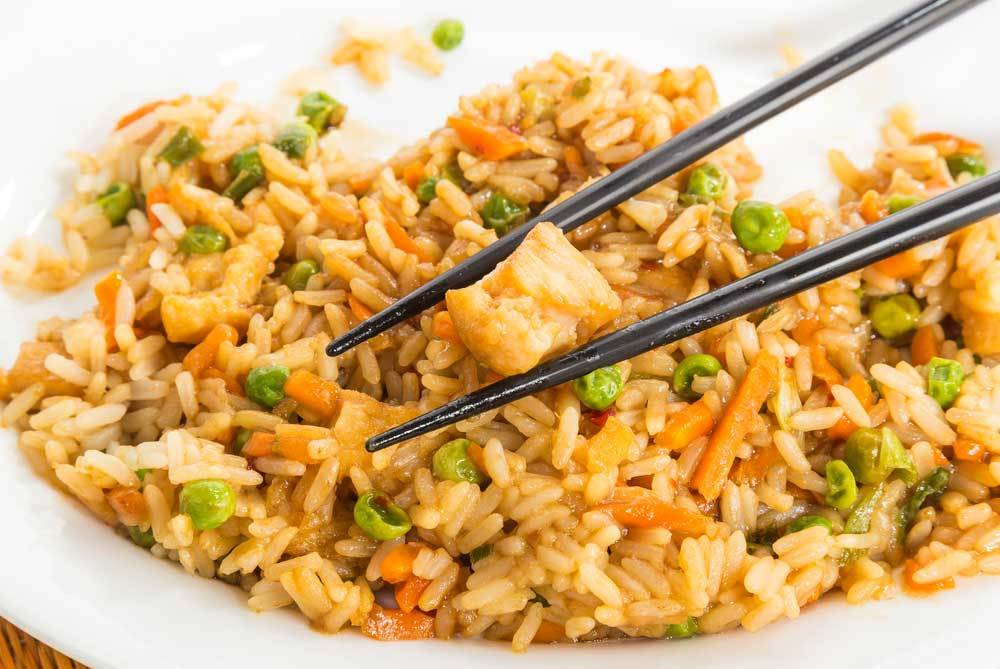Chicken fried rice with a cube of chicken being picked up by a pair of chopsticks
