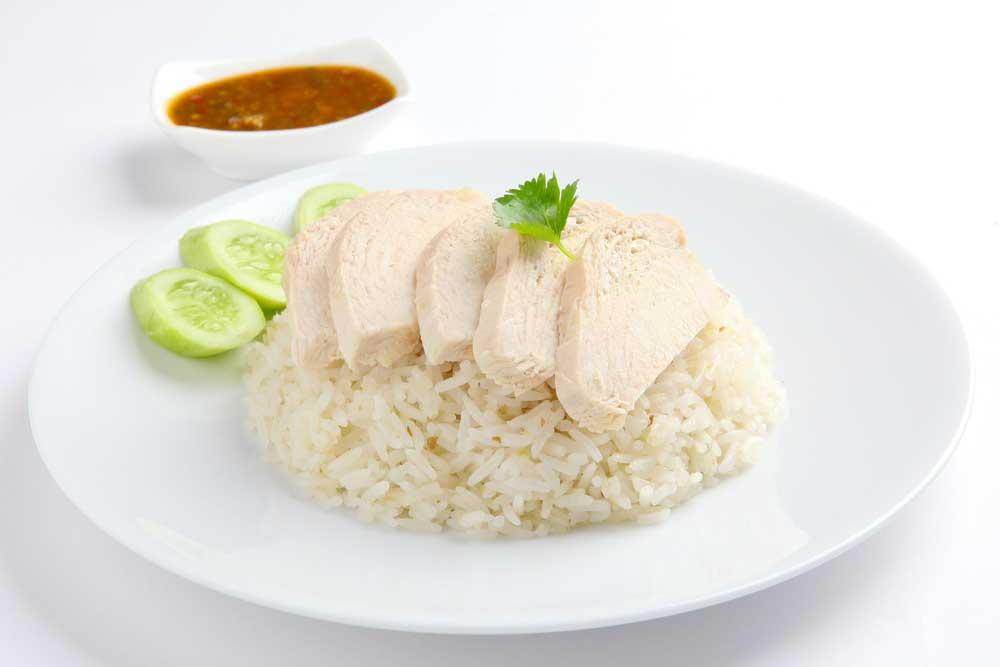 sliced chicken over bed of rice with cucumber garnish on white plate with dipping sauce in background