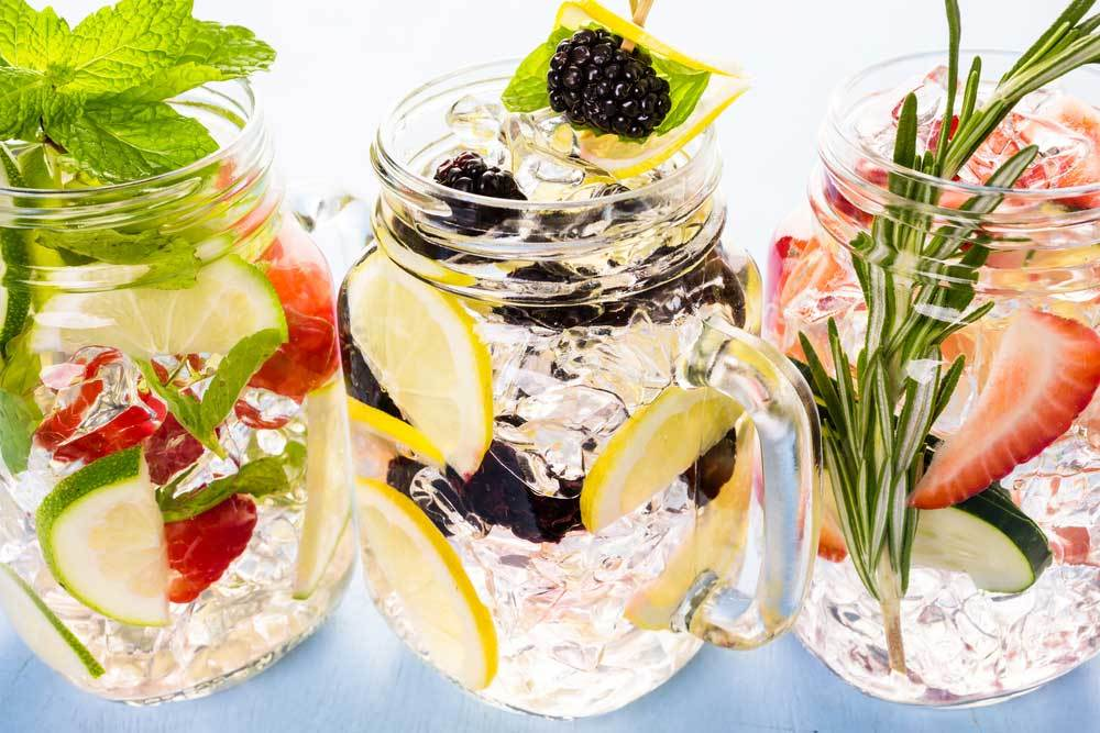 3 glass jars filled with ice and fruit infused water