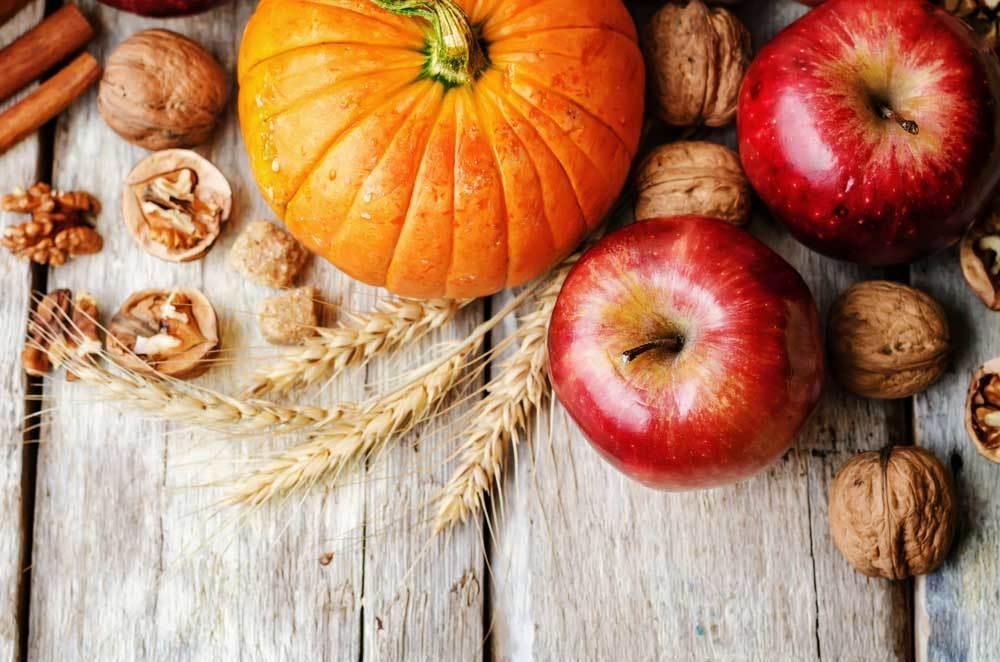 Pumpkin, Apples, walnuts, cinnamon sticks and wheat stalk arranged on a wooden surface