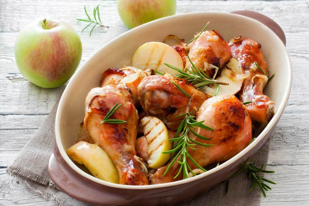 casserole dish containing roasted chicken, apples and rosemary