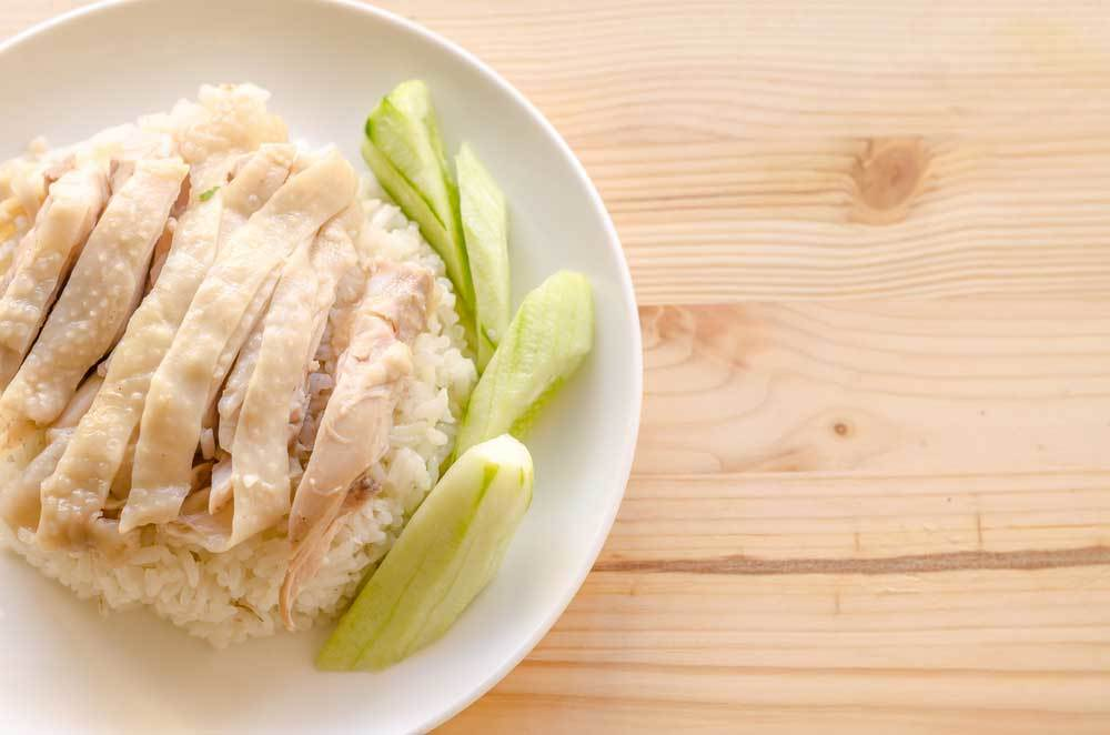 plate of chicken over white rice with cucumber garnish on honey colored wood table top