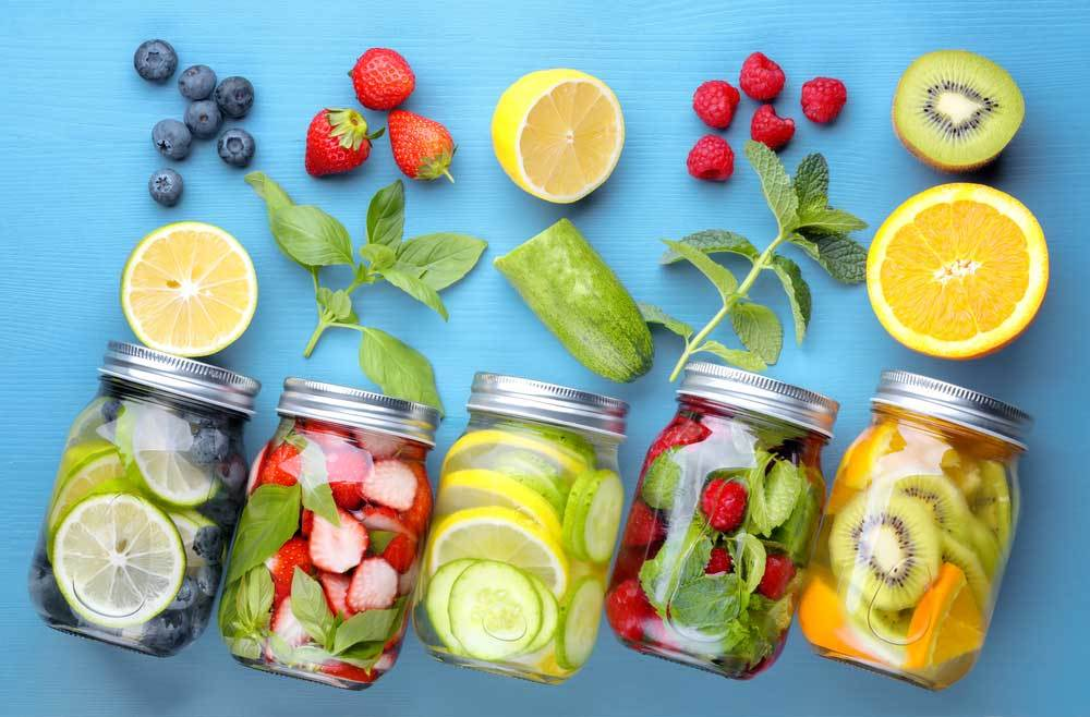 5 jars of fruit water laying on their sides with fruit scattered around on a blue background
