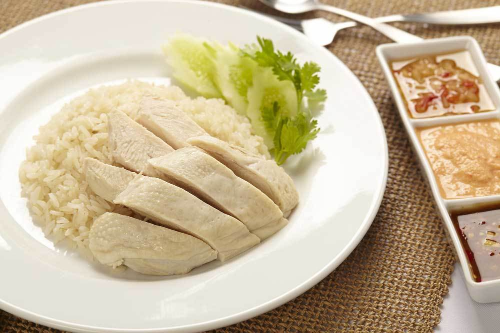 Chicken and white rice with garnish on white plate with side of dipping sauces