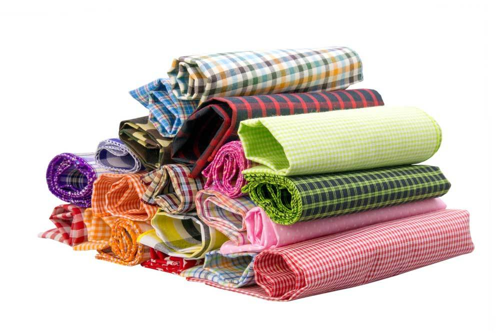 Rolls of multi patterned fabric on white background