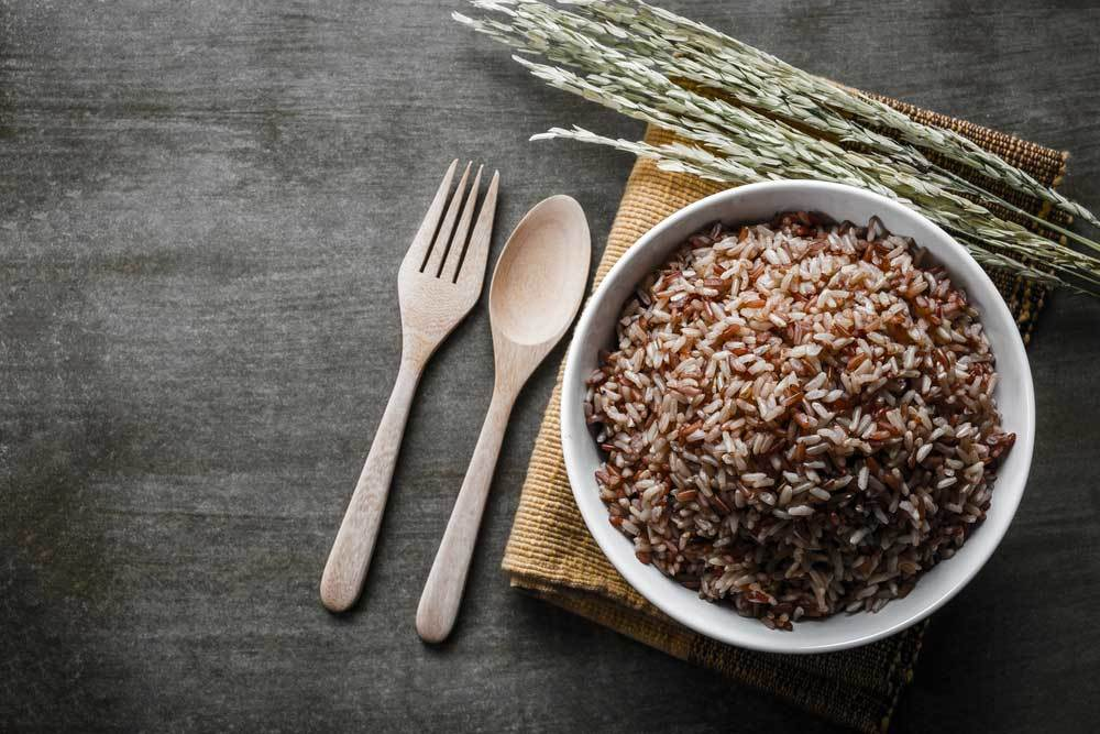 Brown rice in a white bowl on a wooden table surface with stalks of rice and wooden spoon and fork on a burlap place mat