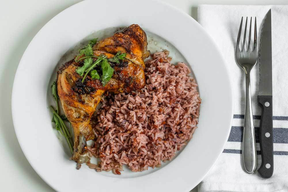 Grilled chicken leg quarter with brown rice and garnish on white plate with napkin, fork and knife