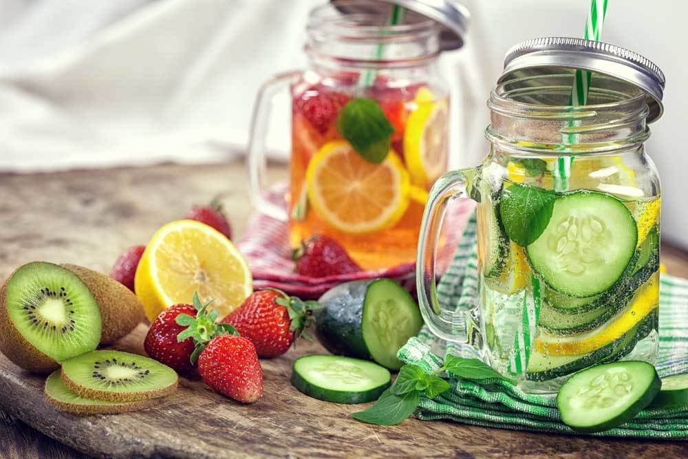 2 jars of fruit infused water with fruit scattered around on a wooden table