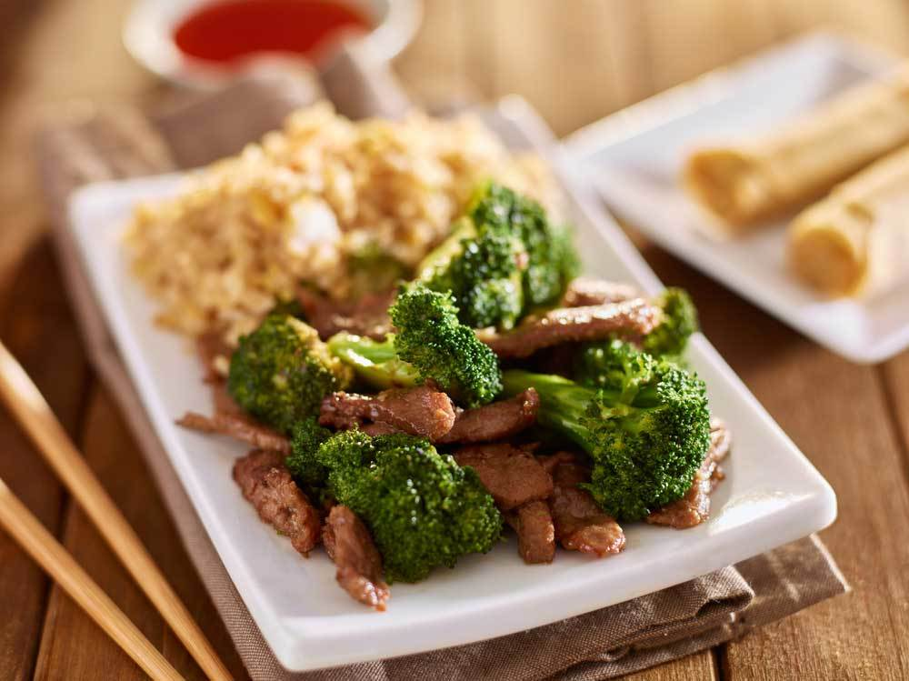 beef and broccoli with brown rice on rectangle plate with condiments and egg rolls in background