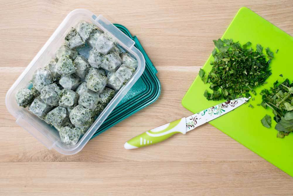 cutting board with fresh chopped mint sitting next to a storage container of mint ice cubes